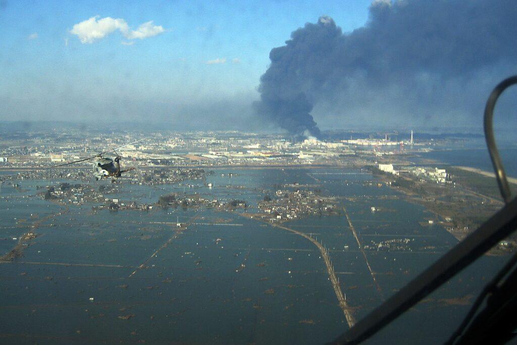 На горизонте горит японский нефтеперерабатывающий завод, пожар возник после землетрясения и цунами. Часть города рядом с ним затоплена. Вне Фукусимы стихия унесла тогда 18,5 тысячи жизней и уничтожила и повредила массу объектов инфраструктуры. Но об этом никто не помнит: все вспоминают только Фукусиму и радиацию, хотя от нее на этой АЭС и вокруг не умер ни один человек / ©Wikimedia Commons